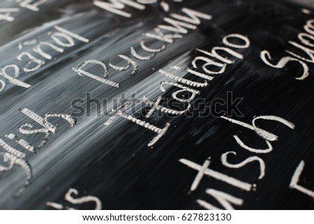 "Inscription on a black chalk board: focused on ""italian"" in italian language, ""russian"" written in russian language, and others parts of names of different languages written in these languages #627823130"