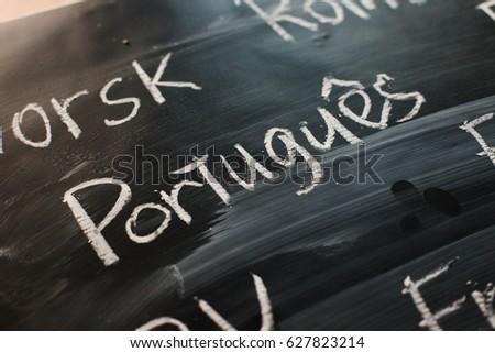 Inscription on a black chalk board: Written in portuguese language: portuguese #627823214