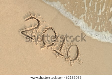 "Inscription ""2010"" on sand. Sea coast with a rolling wave on an inscription #62183083"