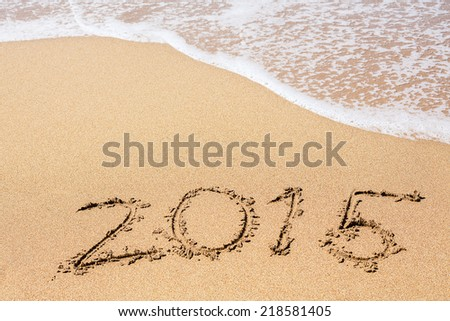 Inscription 2015 on sea sand beach against wave foam. Vacation concept #218581405