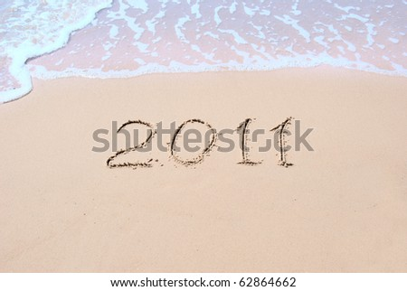 "Inscription ""2011"" on wet sand and a sea wave"