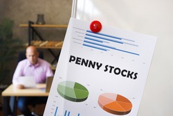 inscription PENNY STOCKS on the printout with diagrams and tables. A successful businessman with documents on the background
