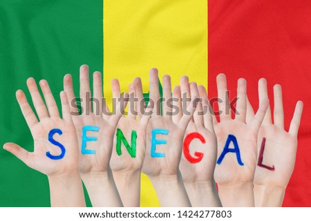 Inscription Senegal on the children's hands against the background of a waving flag of the Senegal #1424277803