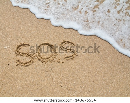 "Inscription ""SOS"" on sand and a sea wave #140675554"