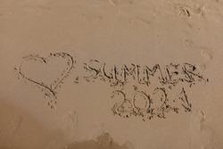 Inscription SUMMER 2021 is written on wet sand. Tourist summer season 2021 concept
