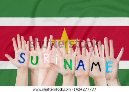 Inscription Suriname on the children's hands against the background of a waving flag of the Suriname #1424277797