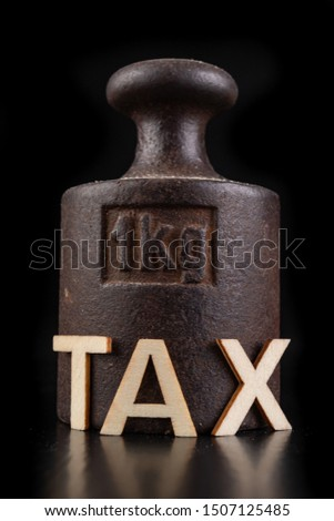 Inscription tax and old weight 1 kilogram. Office and shop accessories on a dark table. Black background. Stok fotoğraf ©