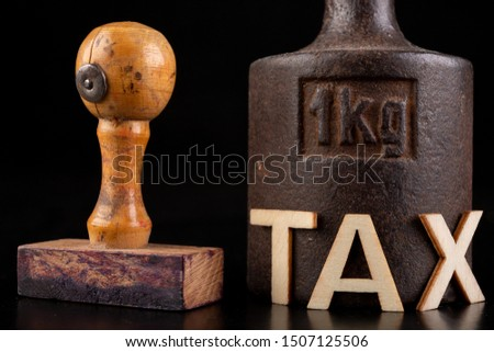 Inscription tax and old weight 1 kilogram. Stamp and store accessories on a dark table. Black background. Stok fotoğraf ©