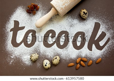 Inscription – to cook, written by flour. On the brown background. #613957580