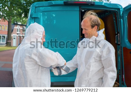 Insect exterminators  dress up in airtight working clothes in residential area