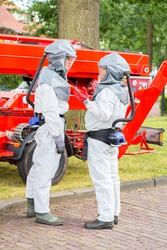 Insect killers in protective working clothes talking together