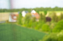 Insect repellentas a mosquito net on the window. blurry view of blue sky and green meadow