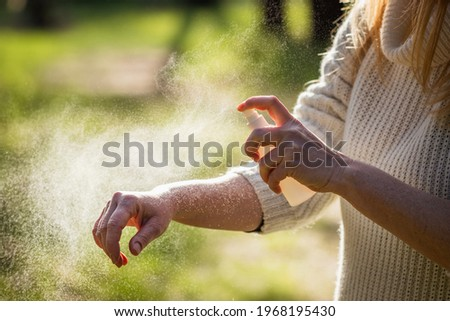 Insect repellent. Woman tourist applying mosquito repellent on hand during hike in nature. Skin protection against tick and mosquito bite Photo stock ©