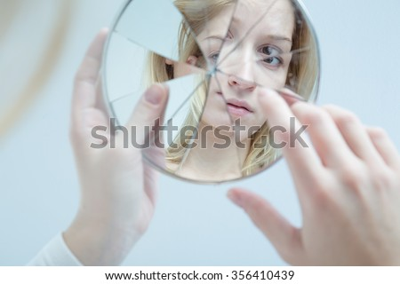 Insecure pretty young woman holding broken mirror Сток-фото ©