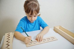 Insert templates for preparing the preschooler's hands for writing. Early development concept. The girl is learning to write
