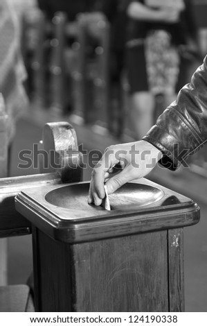 Inserting a banknote into offertory box