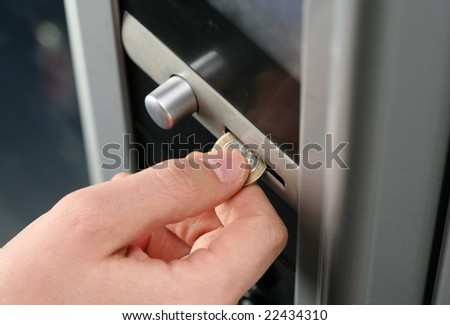 inserting coin in to a vending machine