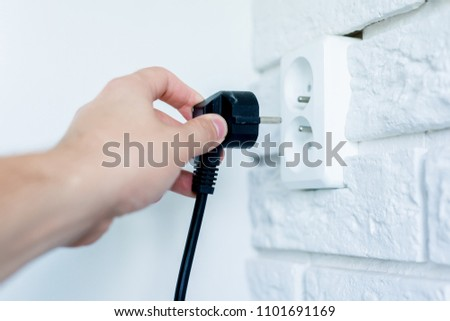 Inserting the plug into the socket. The man holds a black plug in his hand and plugs it into the white socket. The concept of starting an electric device, saving electricity.