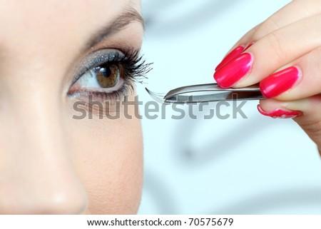 Insertion of false eyelashes. Close up.