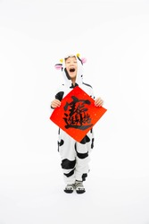 Inside, a boy with a white background wears a cow pajamas and holds a red piece of paper with the words