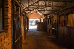 Inside a bricks stable looking trough a door  two hay rolls and horses stals