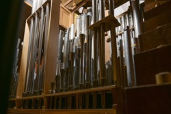Inside a church organ, register with different pipes from metal, musical instrument, selected focus, very narrow depth of field