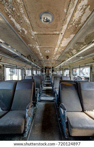 Inside a vintage but abandoned passenger train car with brown cloth and vinyl seats. #720124897