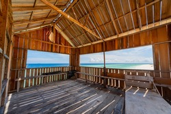 Inside a wooden hut on the beach with wide open window overlooking at the horizon of the sea. Pom Pom Island Sabah.