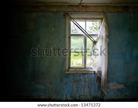 Inside abandoned house. View on broken window with curtain. Grunge scene.