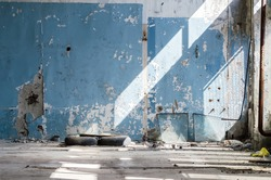 Inside An Old Abandoned Industrial Building, Factory. The Wall With Peeling Blue Paint. Used Tires, Wheels. Many Different Garbage. Broken Glass Unit.