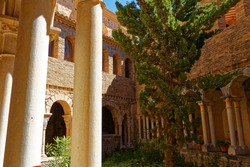 inside an old religious cloister in spain with collumns