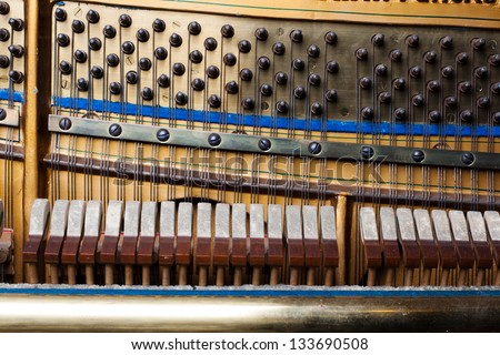 Inside an Upright Piano. Felt Hammers used to strike Steel Strings and wound knobs to tune.