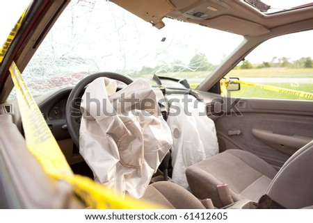 Inside Automobile After Wreck.  Driver and Passenger Air Bags Deployed.  Windshield Shattered with yellow police tape around the vehicle.