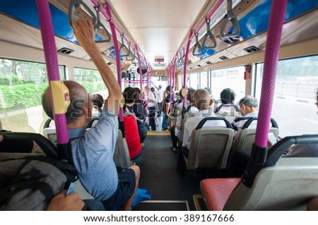 inside bus with many passenger view from the back
