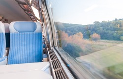 Inside cabin of modern express train. Nobody in blue chairs at window. Motion blur. Comfortable chairs and table in foreground, nature outside window. Travel, France, Europe.