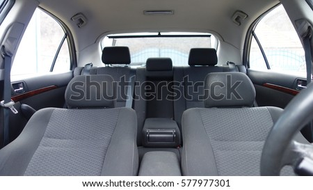Inside car interior with front and back seats, driver and passenger, part from steering wheel, back curtain, fabric, textile, windows, door panels, central arm rest, console #577977301