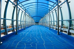Inside of a blue highway overpass, slightly arching. Moody interior with a nice floor pattern.