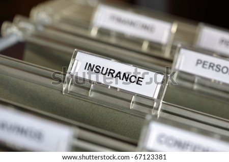Inside of a filing cabinet with green folders and focus on insurance label