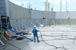 Inside of a large steel tank that is under constructed and have iron bracing  including workers are using the wind to blow water to clean to store chemicals.