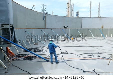 Inside of a large steel tank that is under constructed and have iron bracing  including workers are using the wind to blow water to clean to store chemicals. stock photo