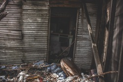 Inside of an old, abandoned white country house filled with trash and a few old appliances.