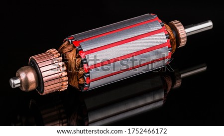 Inside of DC motor rotor with reflection on black background. Artistic still life of dismantled rotary electrical engine. Commutator, wire winding and transformer sheets on shaft. Full depth of field. Foto d'archivio ©