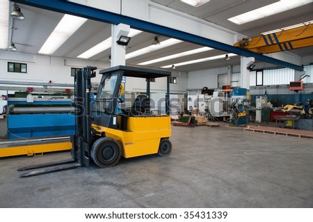 Inside of factory warehouse with forklift and goods