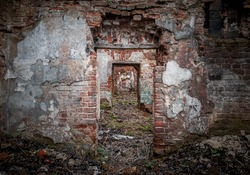 Inside of the mansion ruins. Red brick walls with empty portals. Perspective view of the several doorway,  located one after another inside desolated old building with dirt floor with green grass.