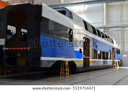Inside of the rail car assembly plant. Industrial workshop for the production of high speed trains. Factory of the manufacturing trainsets passenger rolling stock. Paint shop