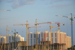 Inside place for many tall buildings under construction and cranes under a blue sky working on place with tall homes