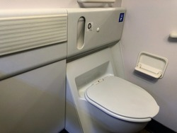 Inside the airplane toilet. Give you a chance to have privacy to handle your nature calls, while are you up in the air. It is a good etiquette to close the cover after used.