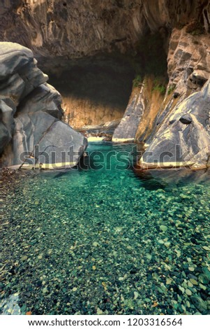 Inside the beautiful cave of Moola Chatok waterfall surrounded by crystal clear water. Khuzdar Balochistan Pakistan.