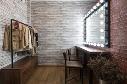 Inside the dressing room in vintage style brick pattern wallpaper wooden table and chairs With a clothes rail, a large mirror and LED lights for makeup and styling.