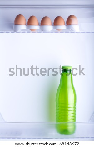 Inside the fridge are five eggs and a bottle of milk